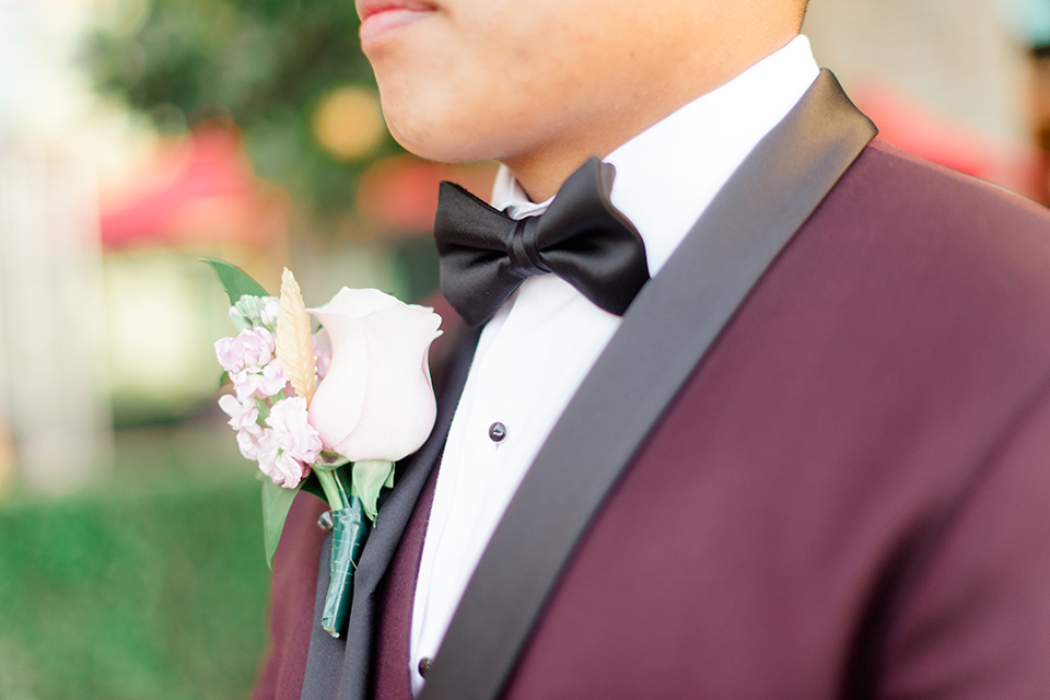 groom in a burgundy tuxedo with a black bow tie