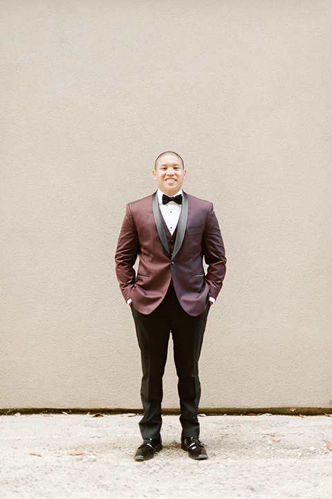 the groom in a burgundy tuxedo with a black bow tie smiling