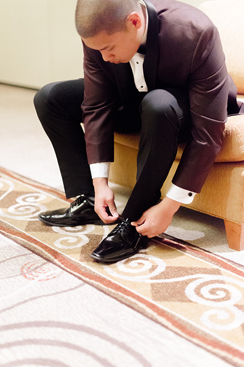 groom in a burgundy tuxedo with a black bow tie close together