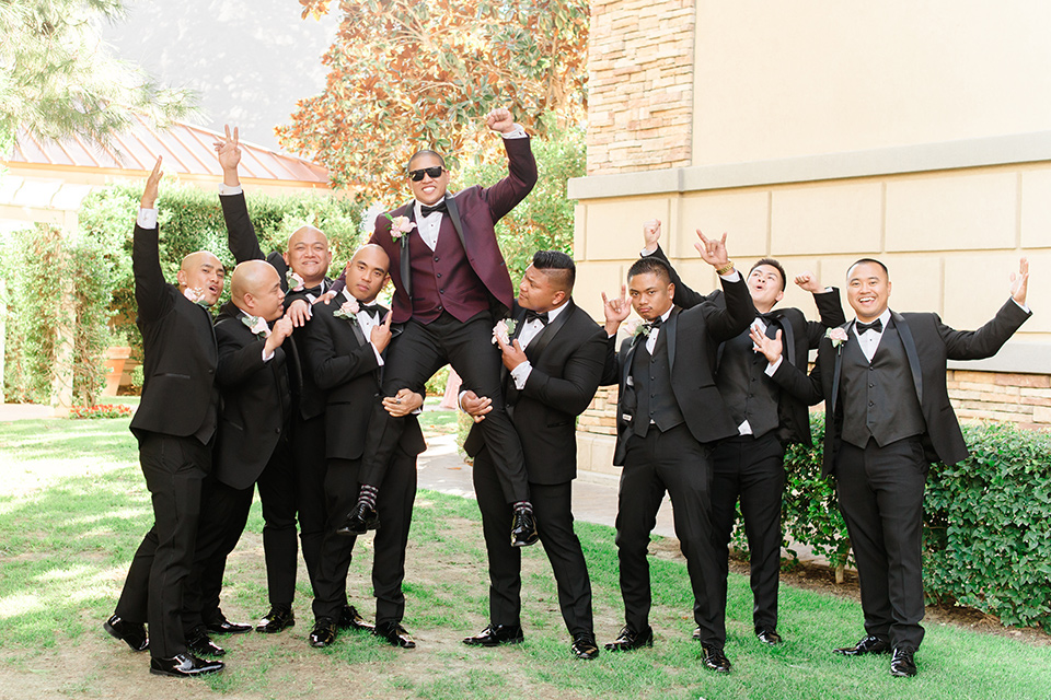 groom in a burgundy tuxedo with a black bow tie and the groomsmen in a black tuxedo with a black bow tie