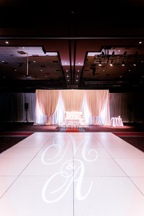 reception décor with a pink lit dancefloor and white linens