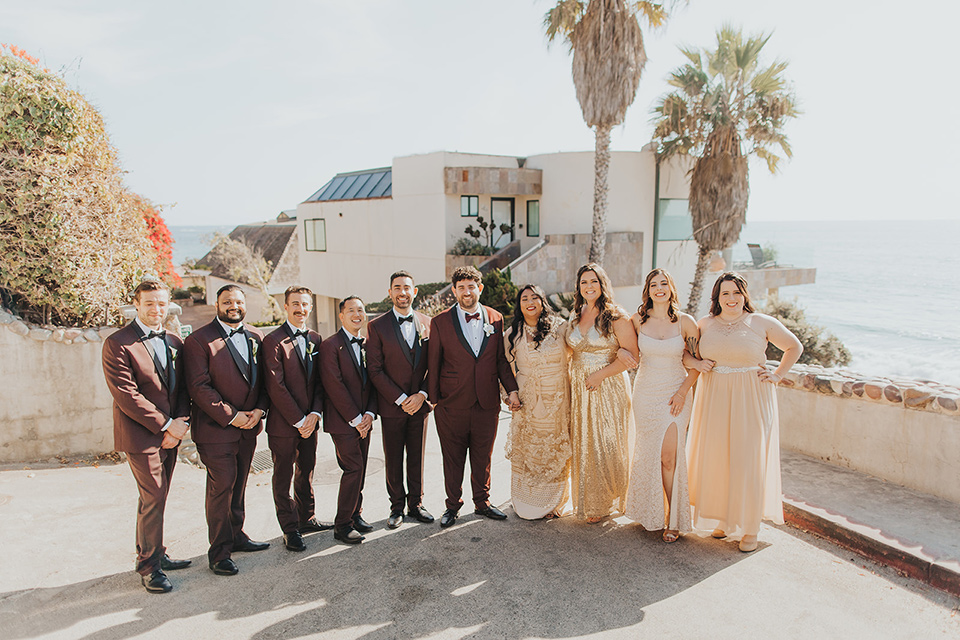 bride in a cultural Burmese gown, the groom in a burgundy tuxedo with a black shawl, the bridesmaids in gold gowns, and the groomsmen in black tuxedos