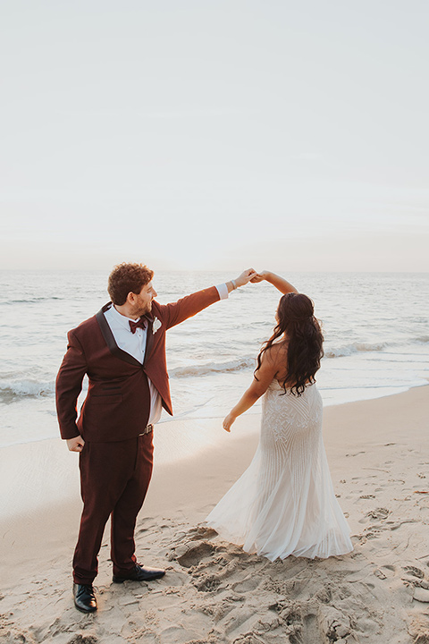 bride in a white lace gown and the groom in a burgundy tuxedo