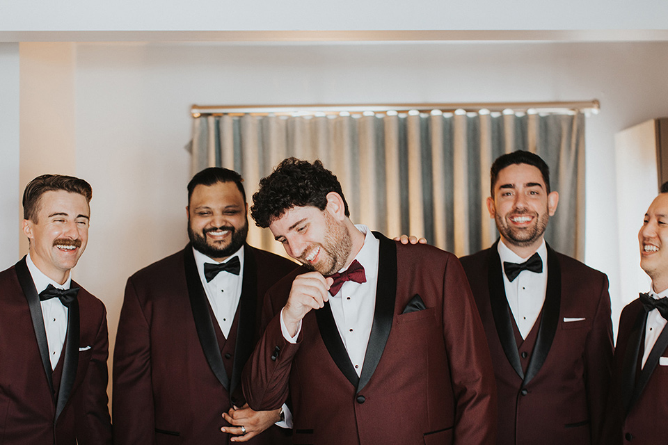 the groom in a burgundy tuxedo with a black shawl and the groomsmen in black tuxedos
