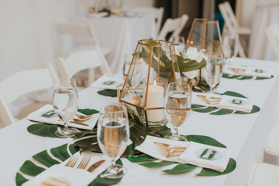 reception tables with gold linens and tropical decor