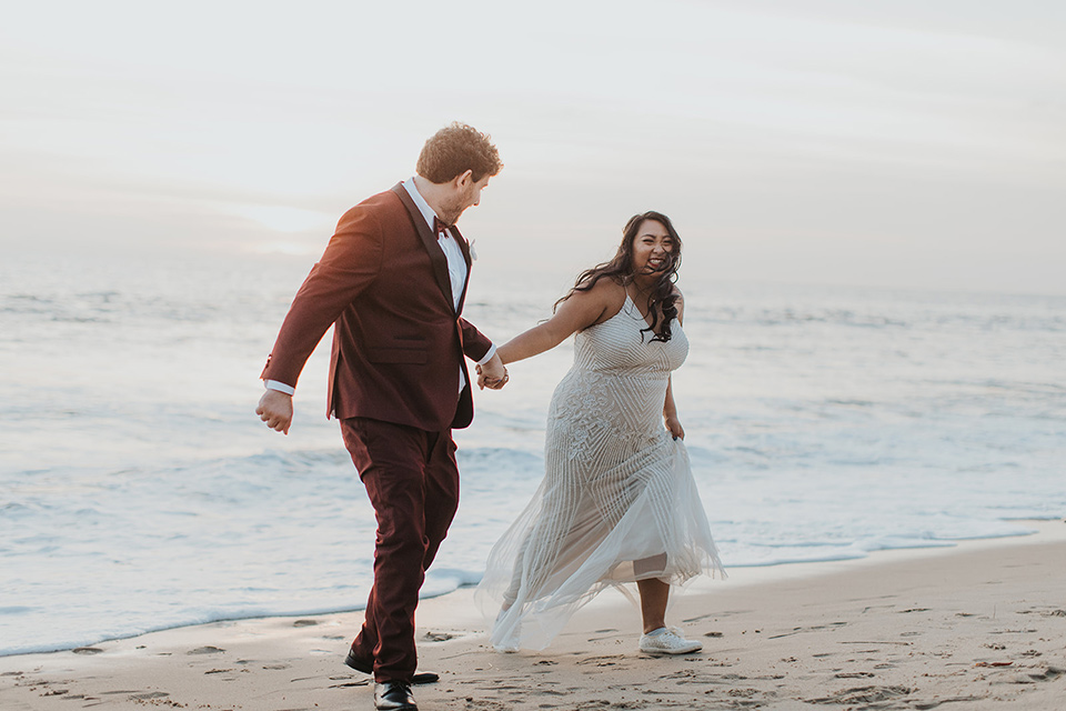 bride in a white lace gown, the groom in a burgundy tuxedo with a black shawl
