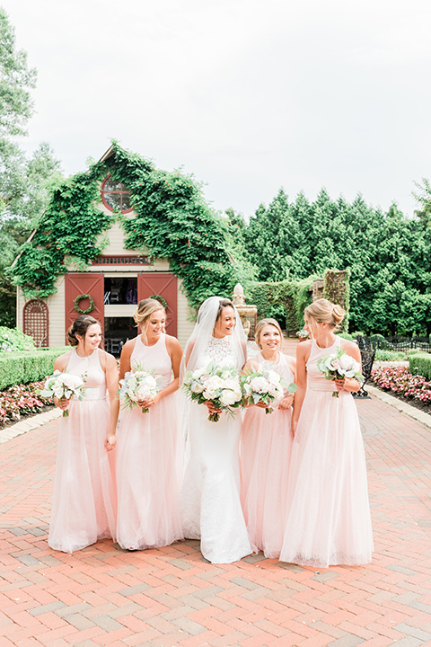 bride in a white lace gown and the groom in a burgundy tuxedo and the bridesmaids in blush toned gowns