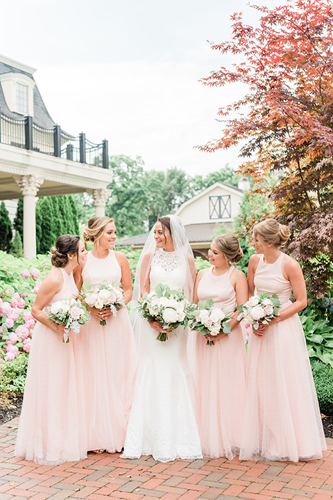 bride in a white modern lace gown with a cathedral veil and bridesmaids in blush toned gowns