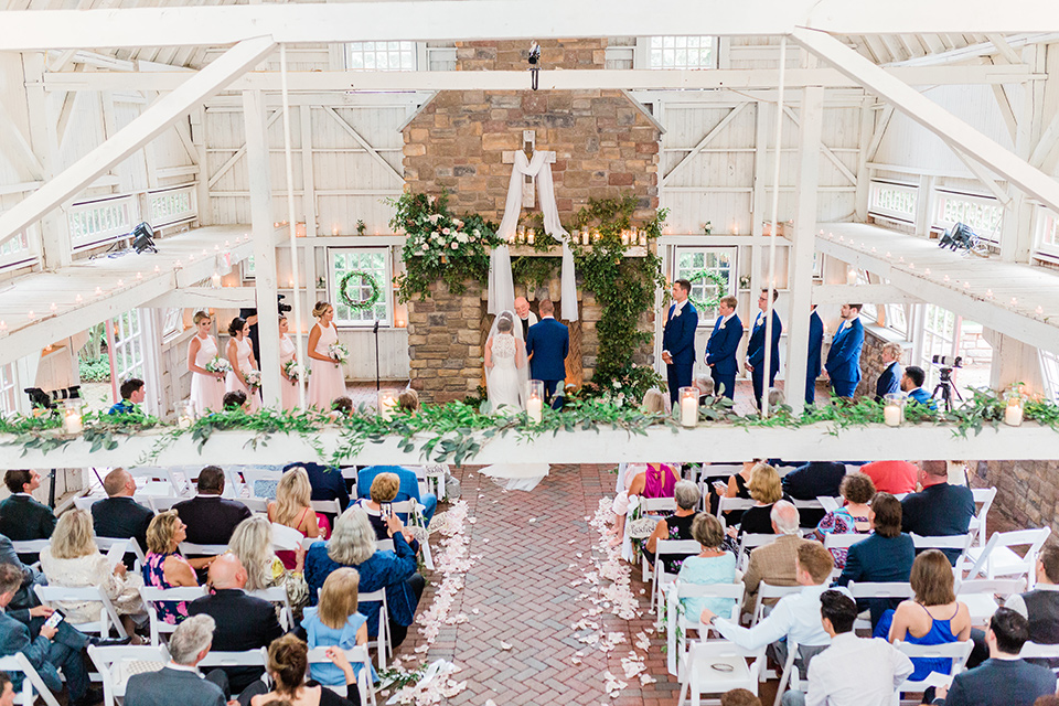 bride in a white modern lace gown with a cathedral veil and the groom in a cobalt blue suit, the bridesmaids in blush pink gown and the groomsmen in cobalt blue suits