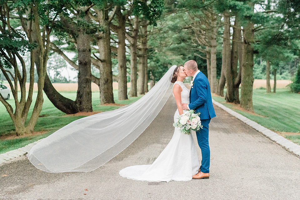 bride in a white modern lace gown with a cathedral veil and the groom in a cobalt blue suit
