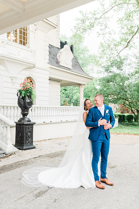 bride in a white lace gown and the groom in a burgundy tuxedo and the bridesmaids in blush toned gowns and the groom in  a cobalt blue suit