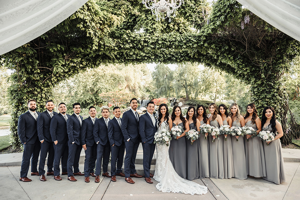 bride in a white formfitting gown and the groom in a navy suit with brown shoes and white long tie, the bridesmaids in light dusty sage gowns and groomsmen in navy blue suits and blue ties
