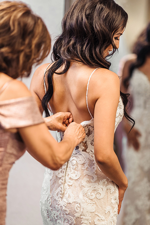 bride in a white lace gown with a crystal bodice and a deep v neckline putting on dress with mom