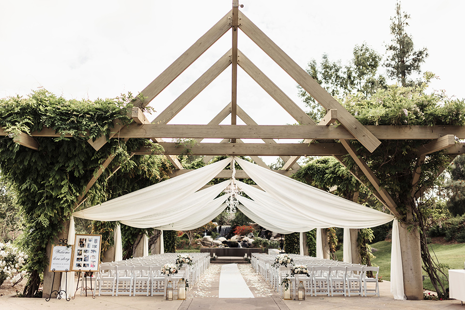 ceremony space under a geometric wooden gazebo with white linens