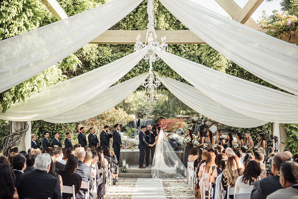 bride in a white formfitting gown and the groom in a navy suit with brown shoes and white long tie, the bridesmaids in light dusty sage gowns and groomsmen in navy blue suits and blue ties at the ceremony