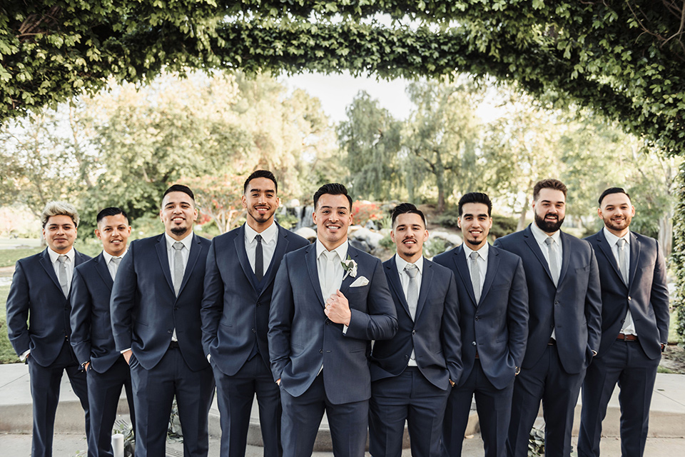 the groom in a navy suit with brown shoes and white long tie and groomsmen in navy blue suits and blue ties