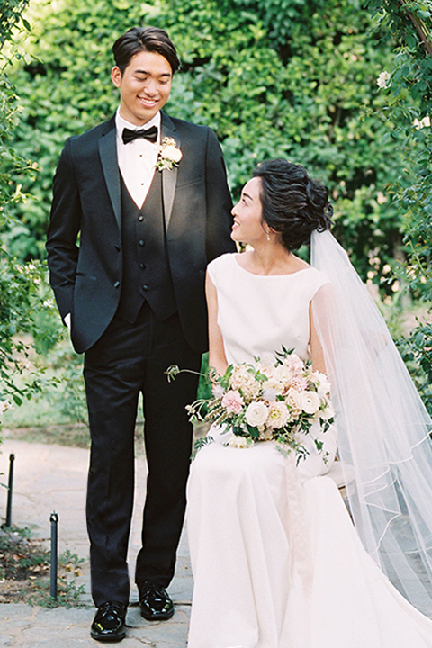 bride in a white formfitting gown with a key hole back detailing and a high neckline and the groom in a sleek black notch lapel tuxedo with a simple black bow tie looking at each other