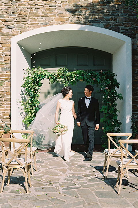 bride in a formfitting white gown with a key hole back and high neck detailing and the groom in a sleek black notch lapel tuxedo with a simple black bow tie at the ceremony