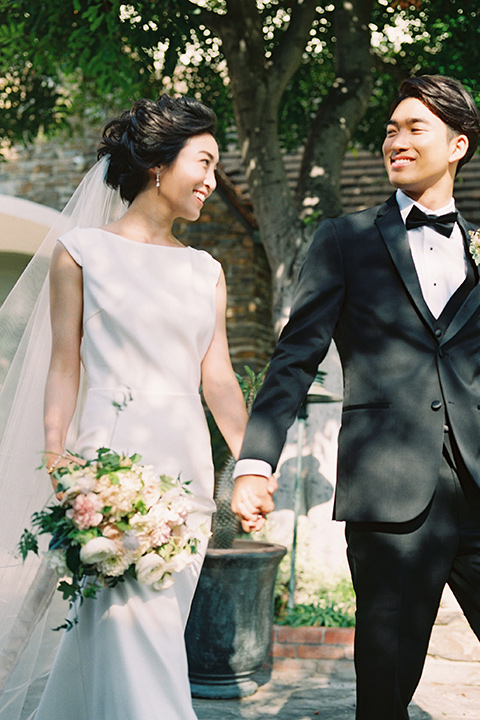 bride in a white formfitting gown with a key hole back detailing and a high neckline and the groom in a sleek black notch lapel tuxedo with a simple black bow tie walking down the aisle