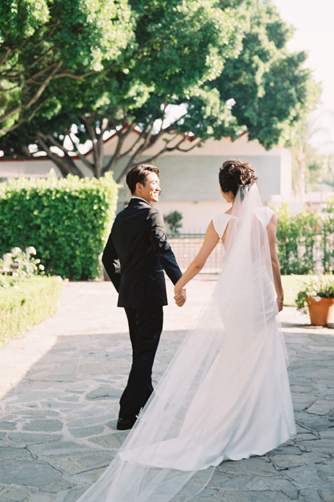 bride in a formfitting white gown with a key hole back and high neck detailing and the groom in a sleek black notch lapel tuxedo with a simple black bow tie walking away from the camera