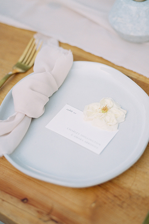 white flatware with white linens on a wooden table