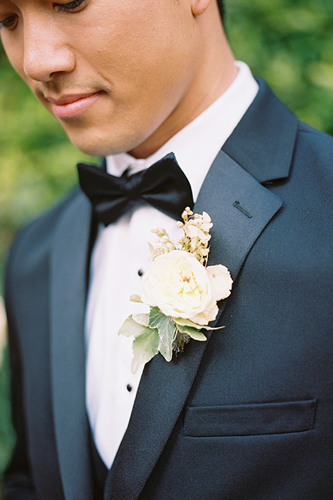 the groom in a sleek black notch lapel tuxedo with a simple black bow tie