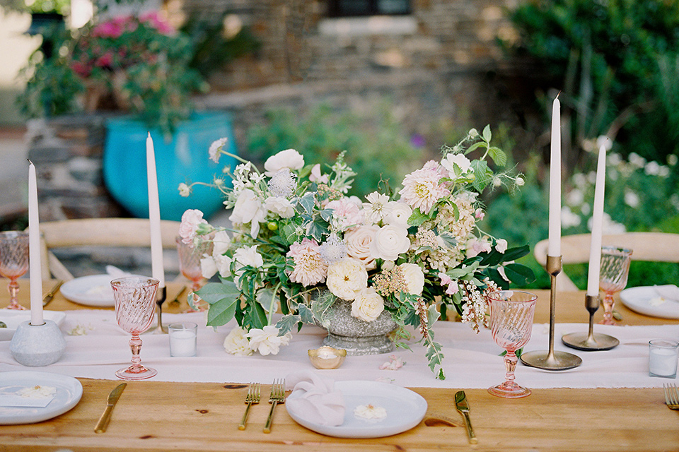 wooden table with tall white candles and white table linens