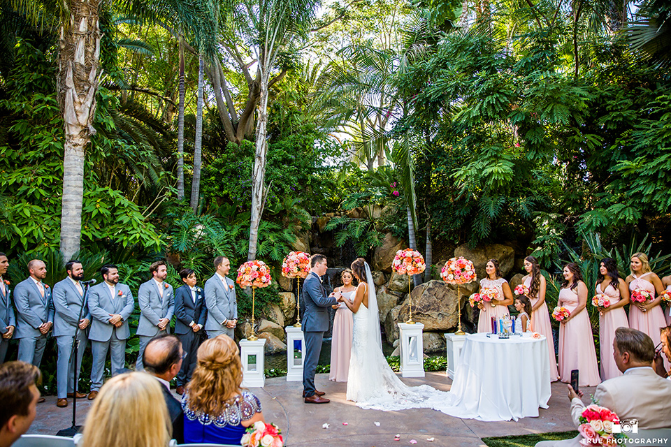 bride in a formfitting lace gown and the groom in a charcoal tuxedo, the bridesmaids in pink gowns, and groomsmen in light blue suits