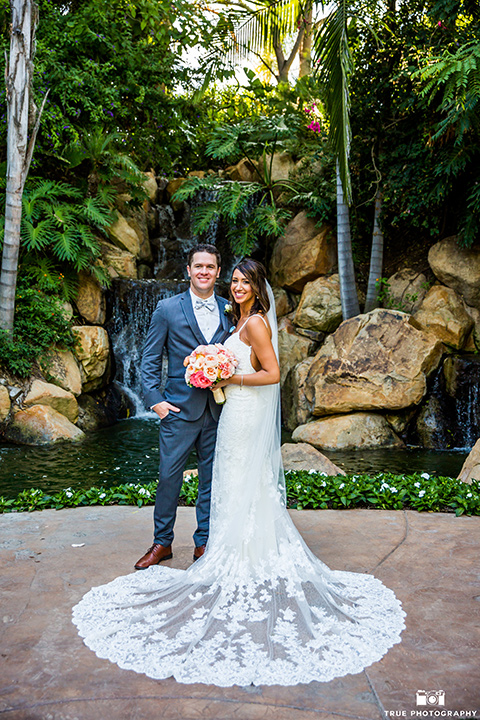 bride in a formfitting lace gown and the groom in a charcoal tuxedo