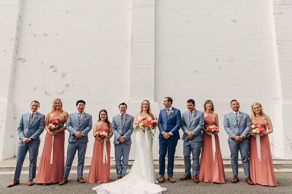 bride in a formfitting lace gown and the groom in a blue suit, the bridesmaids in desert sunset colored gowns, and the groomsmen in light blue suits