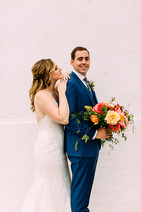 bride in a formfitting lace gown and the groom in a blue suit