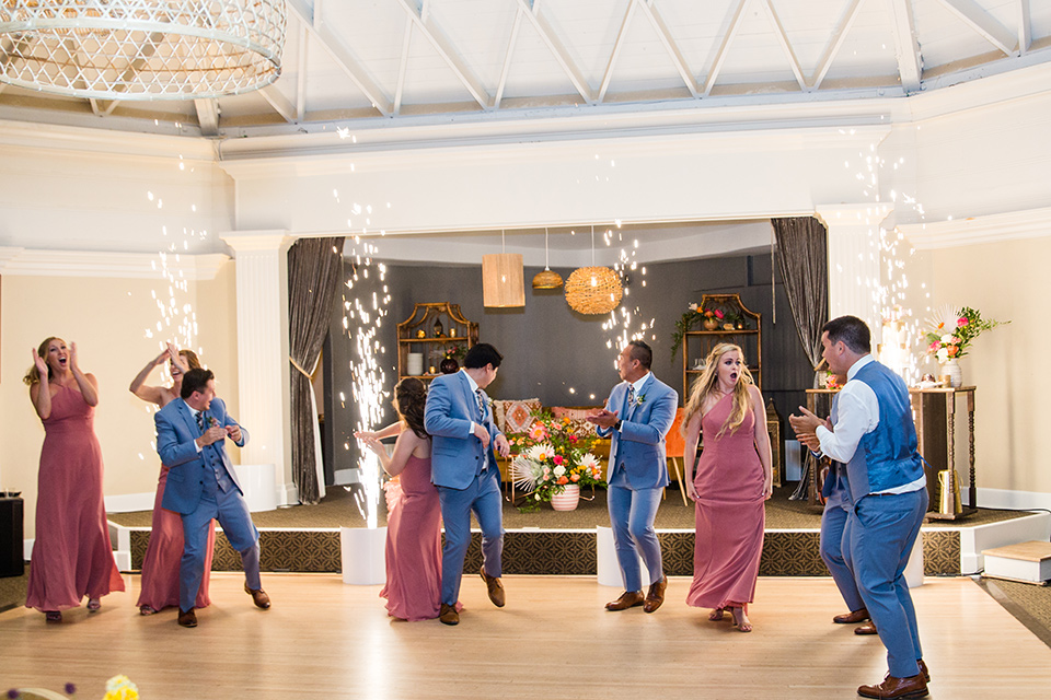 bride in a formfitting lace gown and the groom in a blue suit everyone dancing