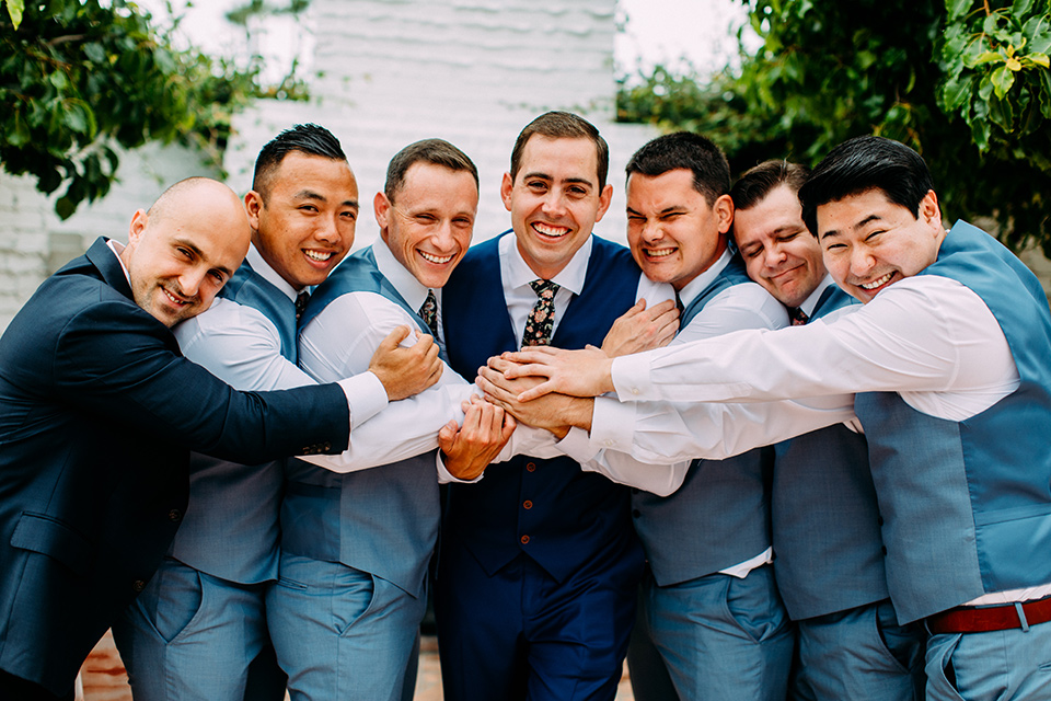 the groom in a blue suit and the groomsmen in light blue suits