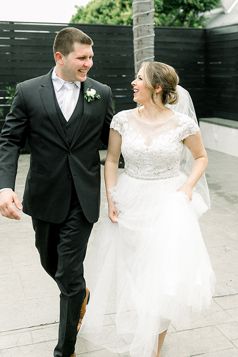 bride in a flowing gown with cap sleeves and the groom in an asphalt groom look