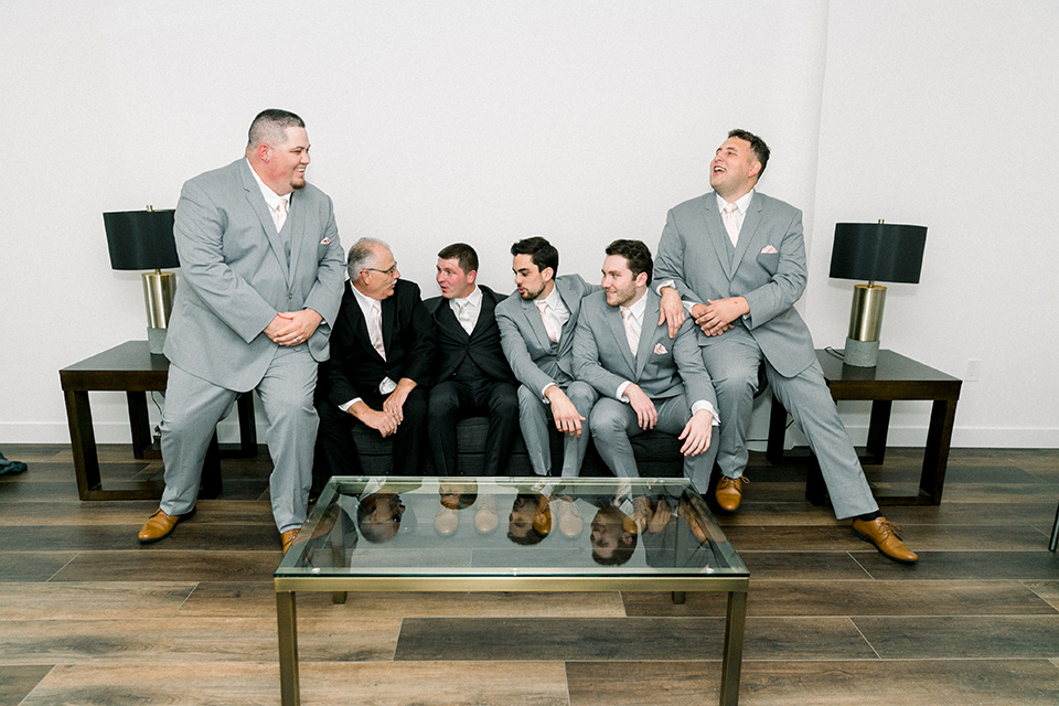 bride in a flowing gown with cap sleeves and the groom in an asphalt groom look, and the bridesmaids in peach gowns and the groomsmen in light grey suits