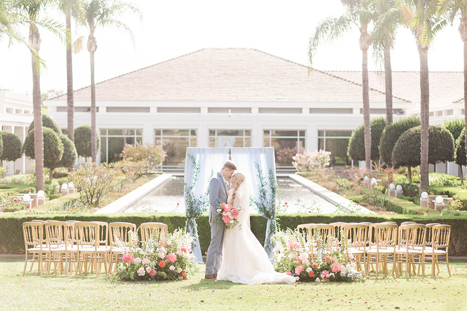 ceremony set up with wooden chairs and pink flowers