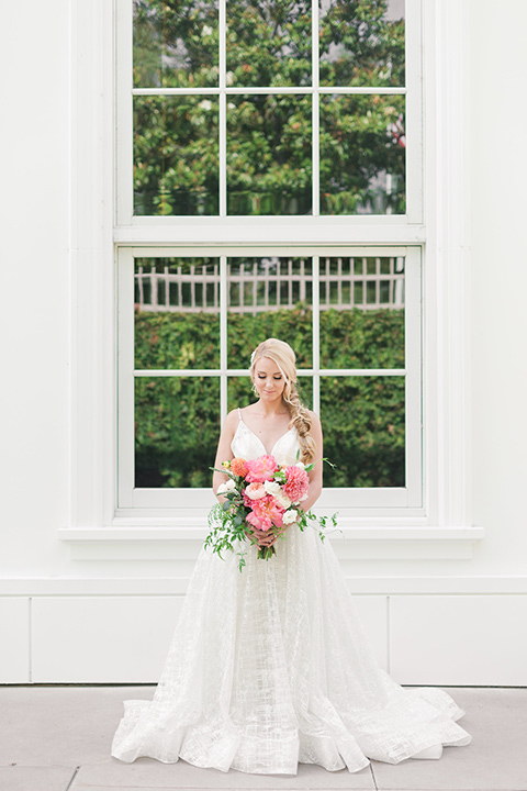 bride in a white lace ballgown with a pink bouquet and hair in a braid