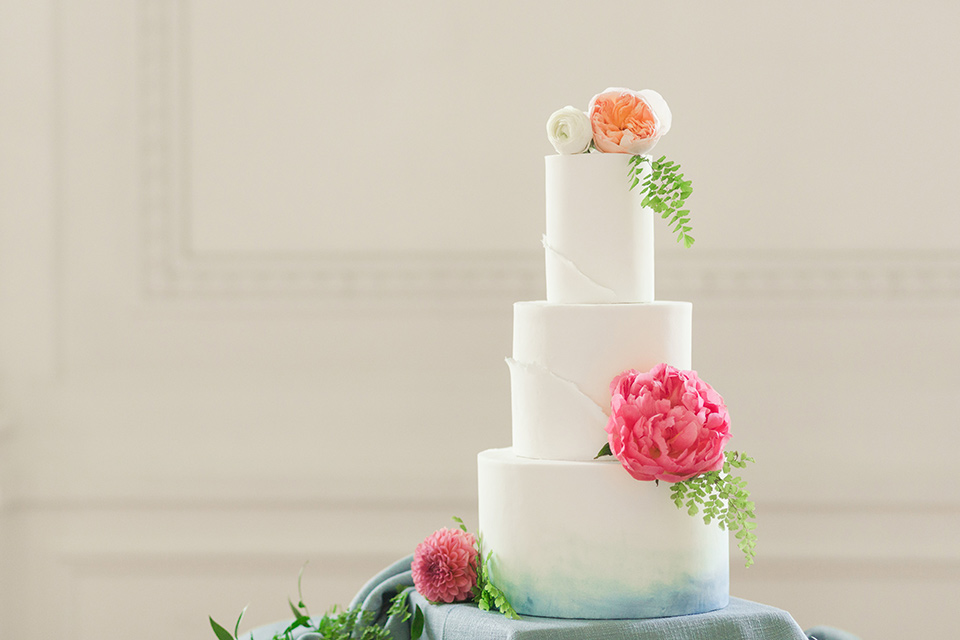 white tiered cake with bright pink and green flowers