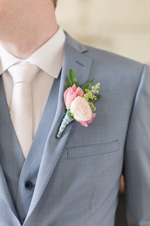 groom in a light blue suit with a pink boutonniere