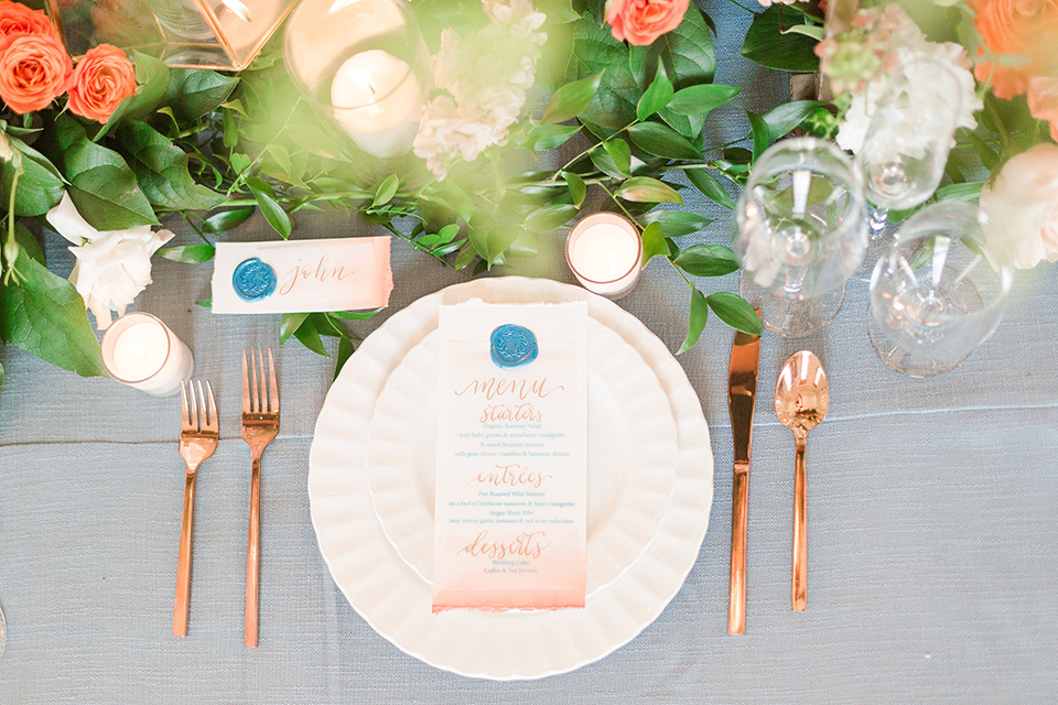 light blue table linens with white plates and gold flatware