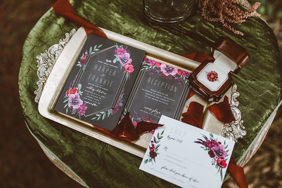 black invitations with pink rose and burgundy floral details and calligraphy
