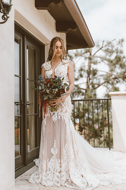 bride in a white lace gown with an illusion neckline and flowing train