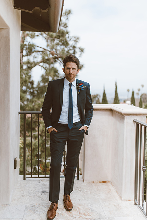 groom in a navy notch lapel suit with a deep teal long tie