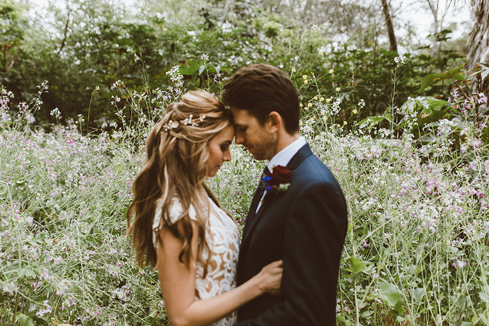 bride in a white lace gown with an illusion neckline and flowing train and the groom in a navy notch lapel suit with a deep teal long tie