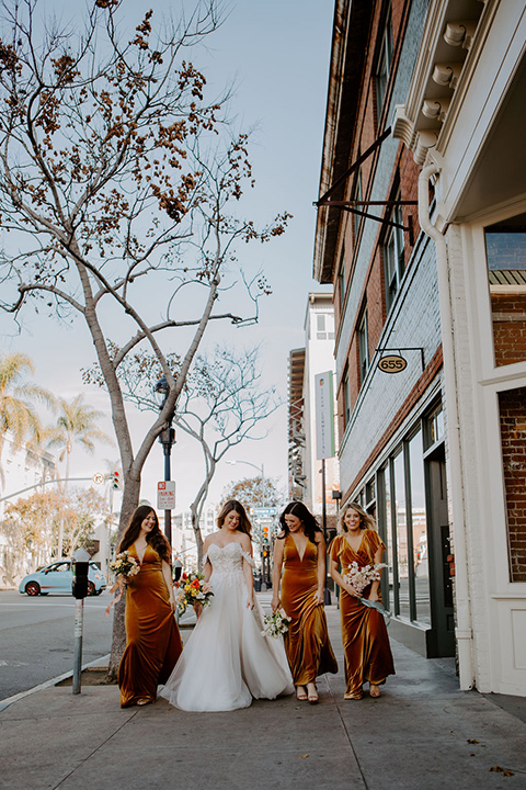 bride in a full skirt gown with an off the shoulder detail and the bridesmaids in burnt orange velvet gowns