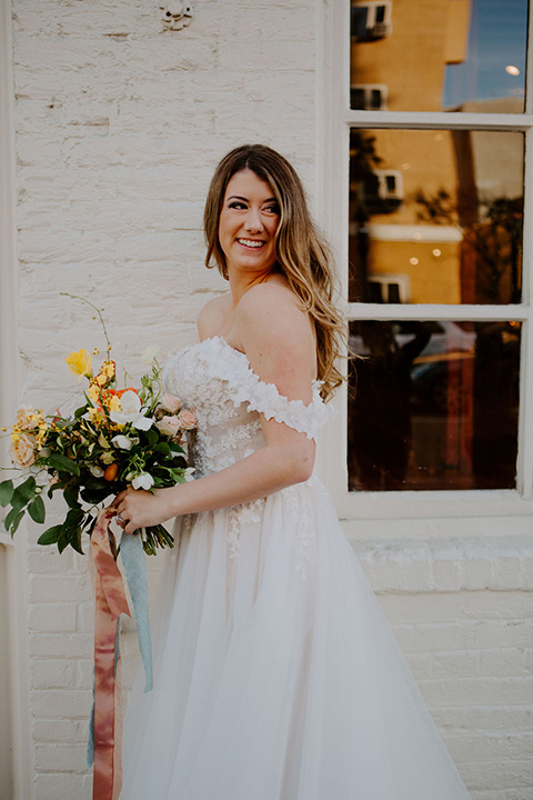 bride in a full skirt gown with an off the shoulder detail