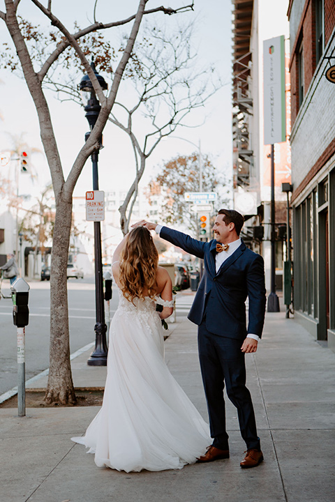 bride in a full skirt gown with an off the shoulder detail and the groom in dark blue suit and bow tie