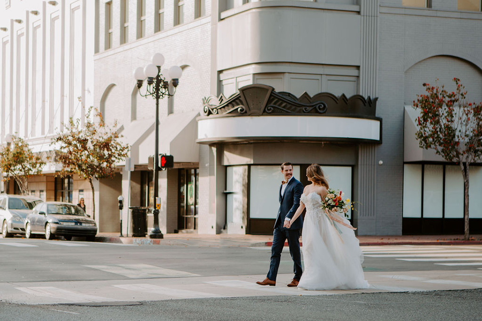 bride and groom crossing the street – bride in a full skirt gown with an off the shoulder detail and the groom in a dark blue suit with a bow tie
