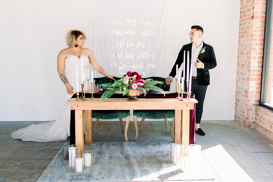 the bride is in a white formfitting lace gown with a sweetheart neckline and fun velvet shoes and the groom in a black velvet tuxedo with a cropped pant and bow tie at sweetheart table