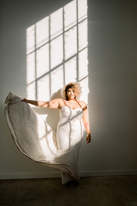 the bride is in a white formfitting lace gown with a sweetheart neckline and fun velvet shoes